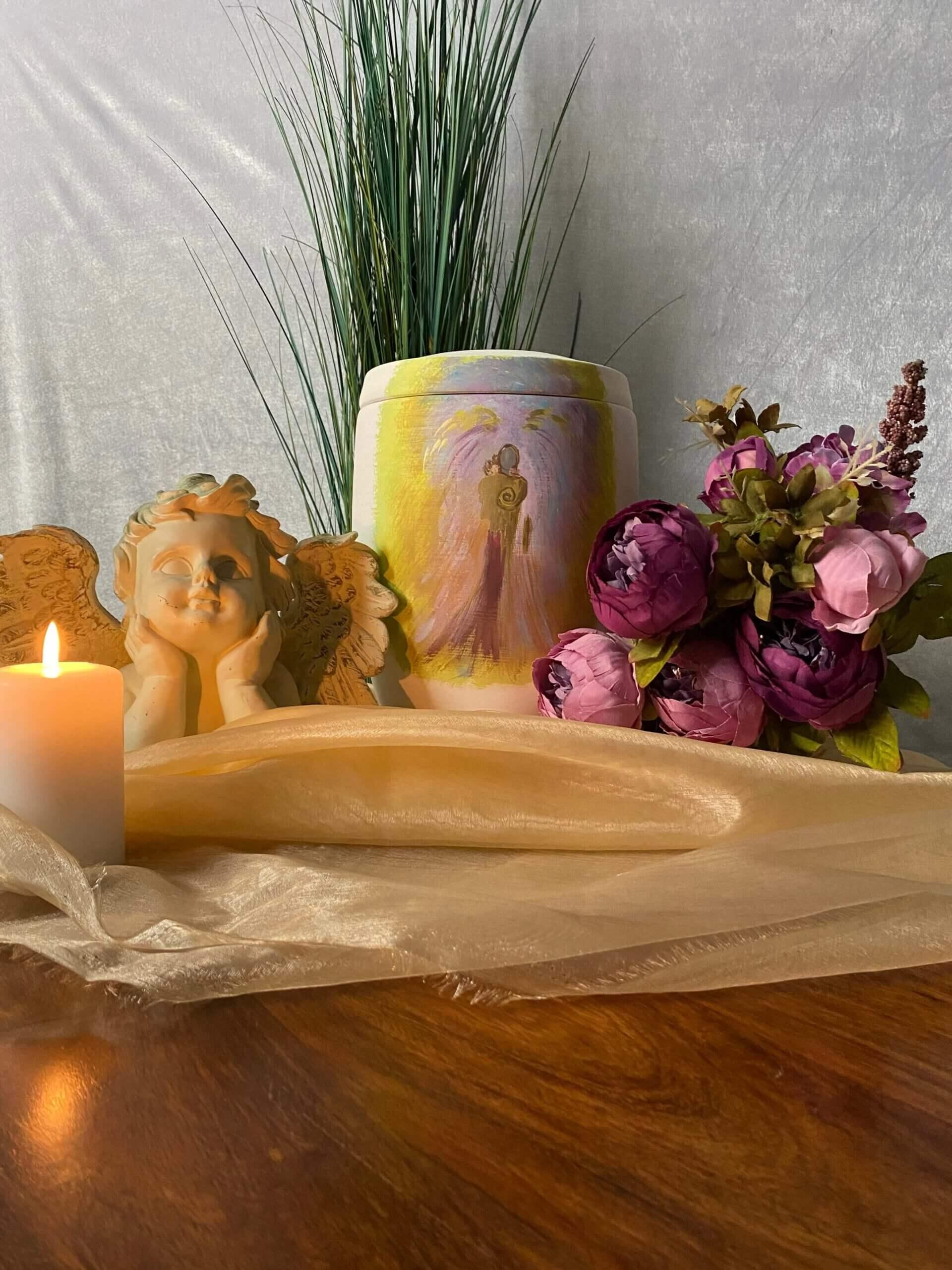 Bunte Urne mit Engelsfigur hinter Kerzenlicht