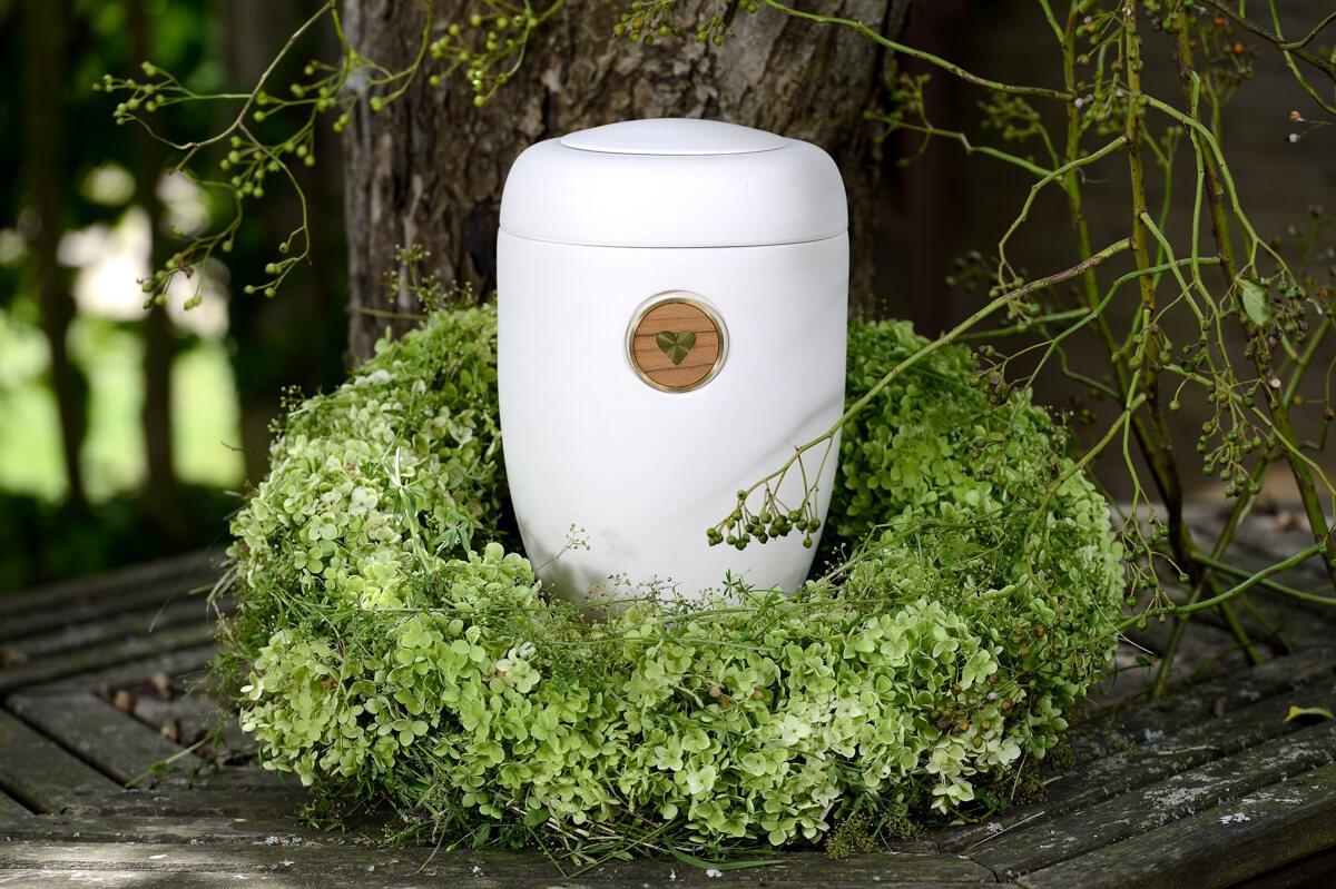 Grünes Herz auf weißer Urne mit Kranz