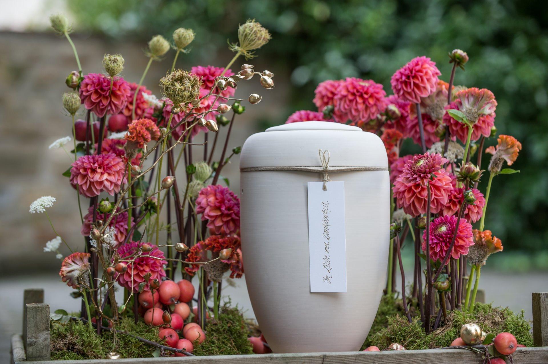 Rote Blumen mit Urne