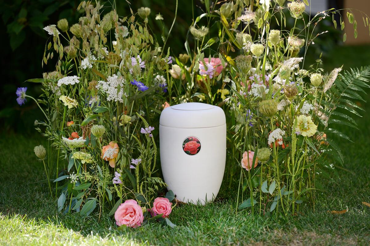Von hohen Blumen umgebene weiße Urne