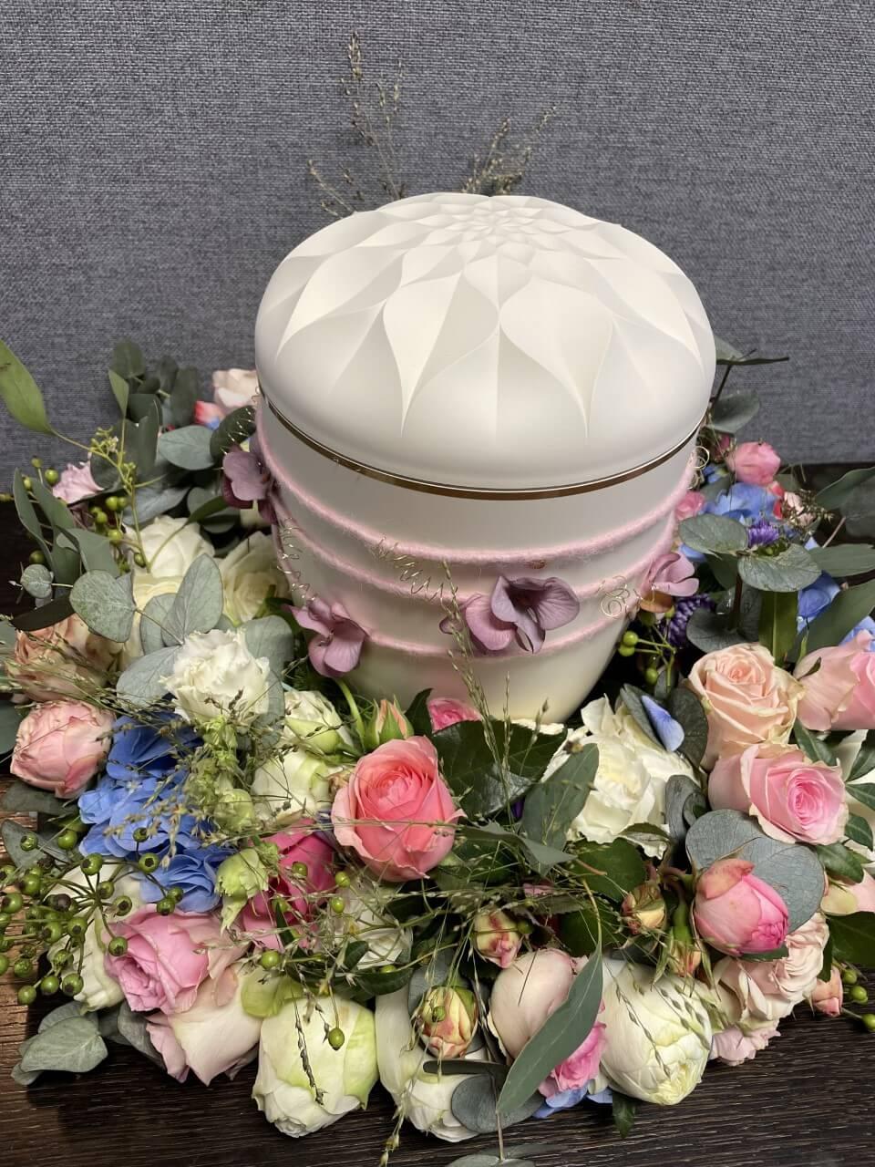 Bunter Blumenkranz mit weißer Urne und rosa Schleife