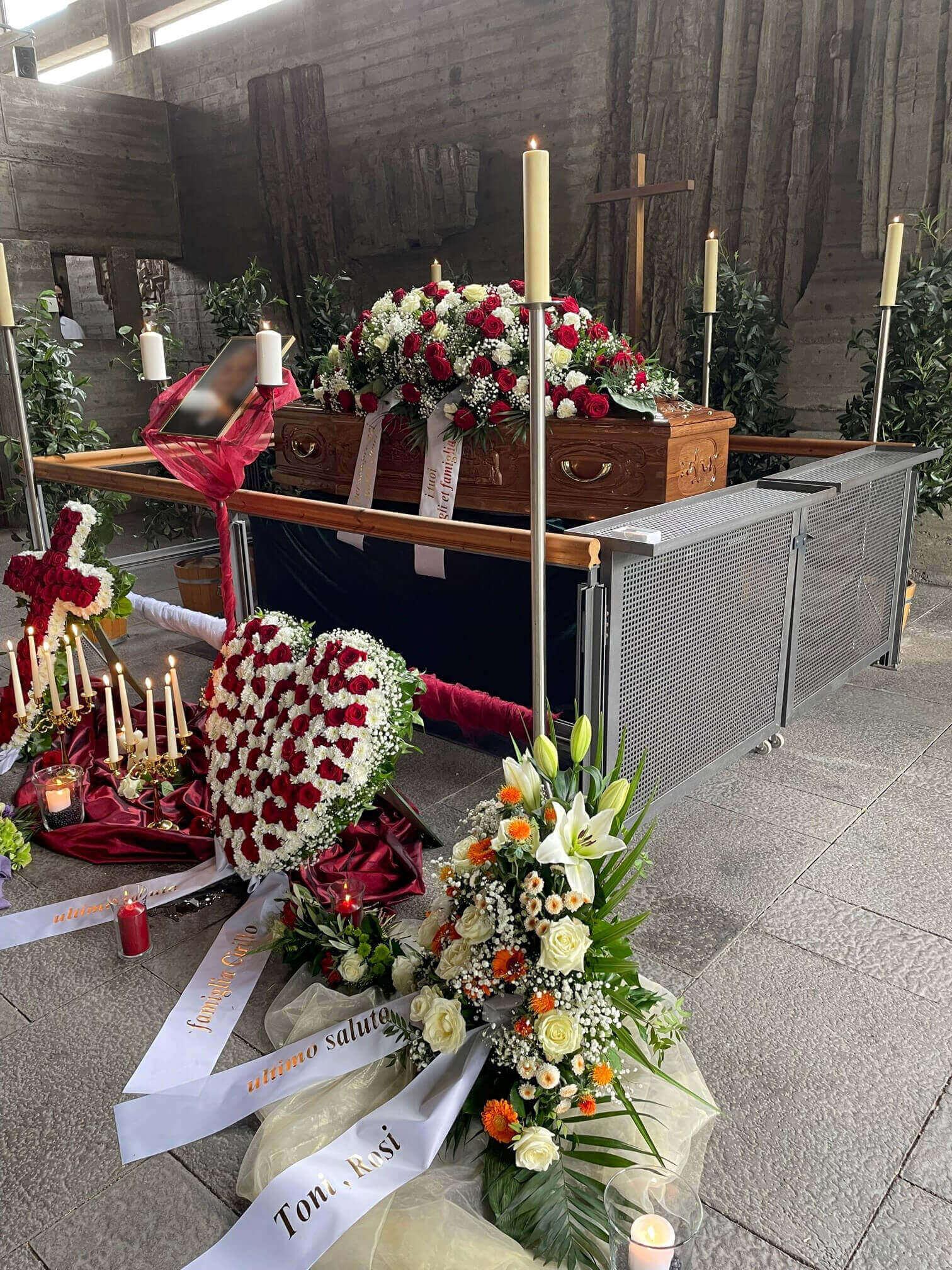 Rot-weiße Blumenbuketts und Trauerkränze um Sarg