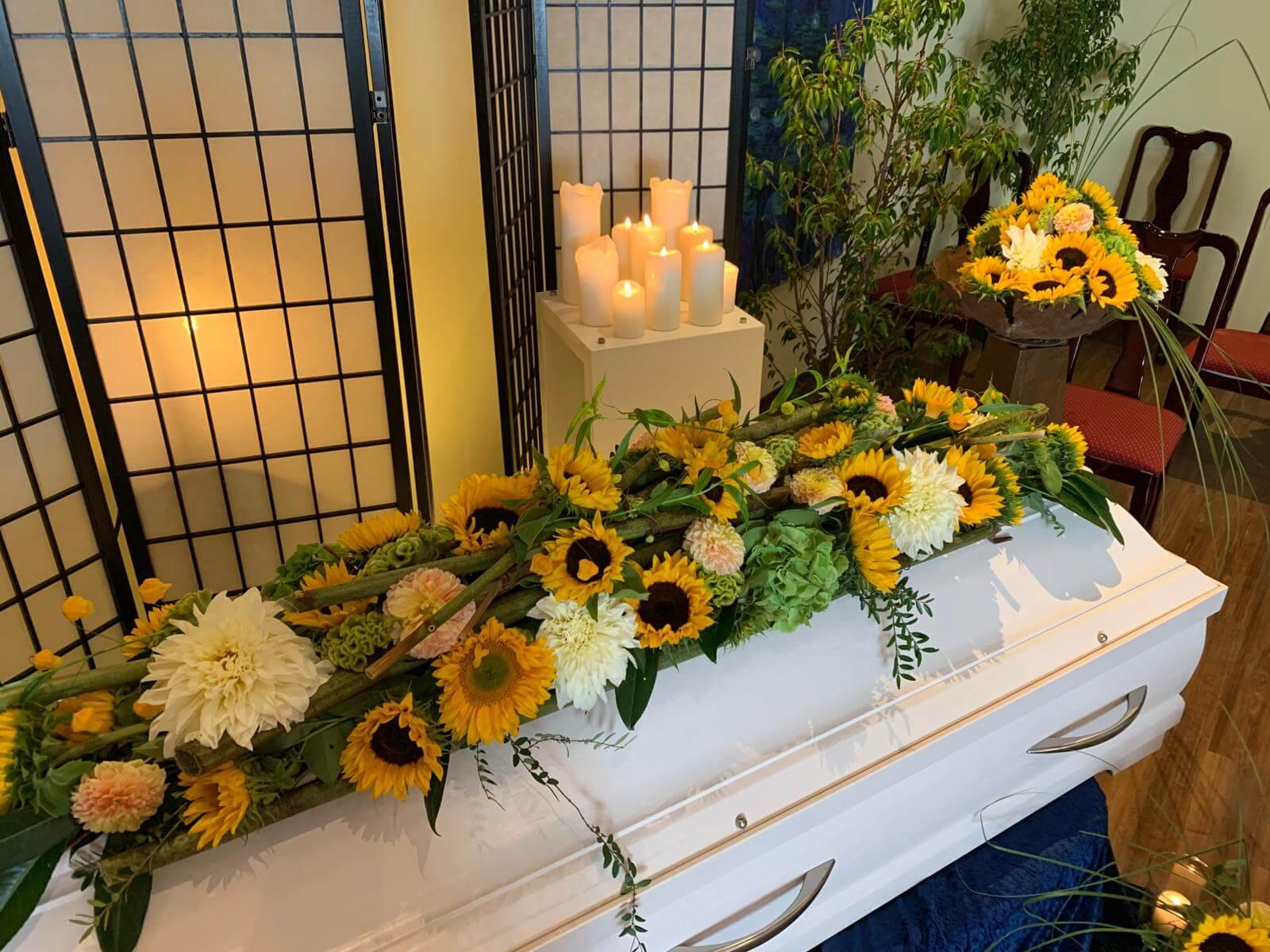Sonnenblumen-Sargbukett auf weißem Sarg