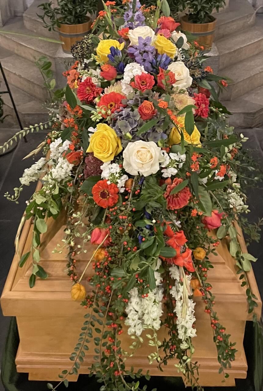 Bunte Blumen als Sargbukett auf braunem Sarg