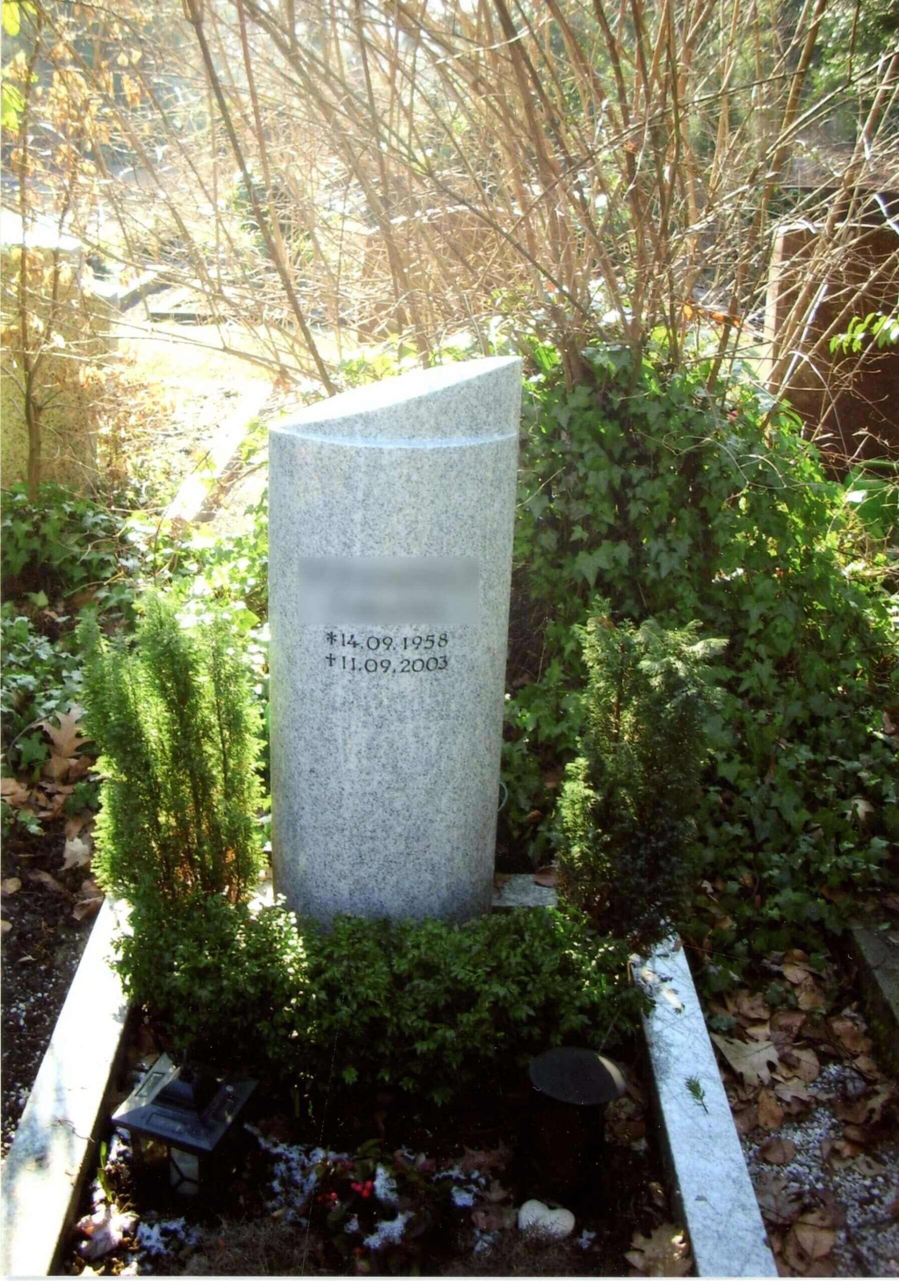 Grauer Grabstein umgeben von grün