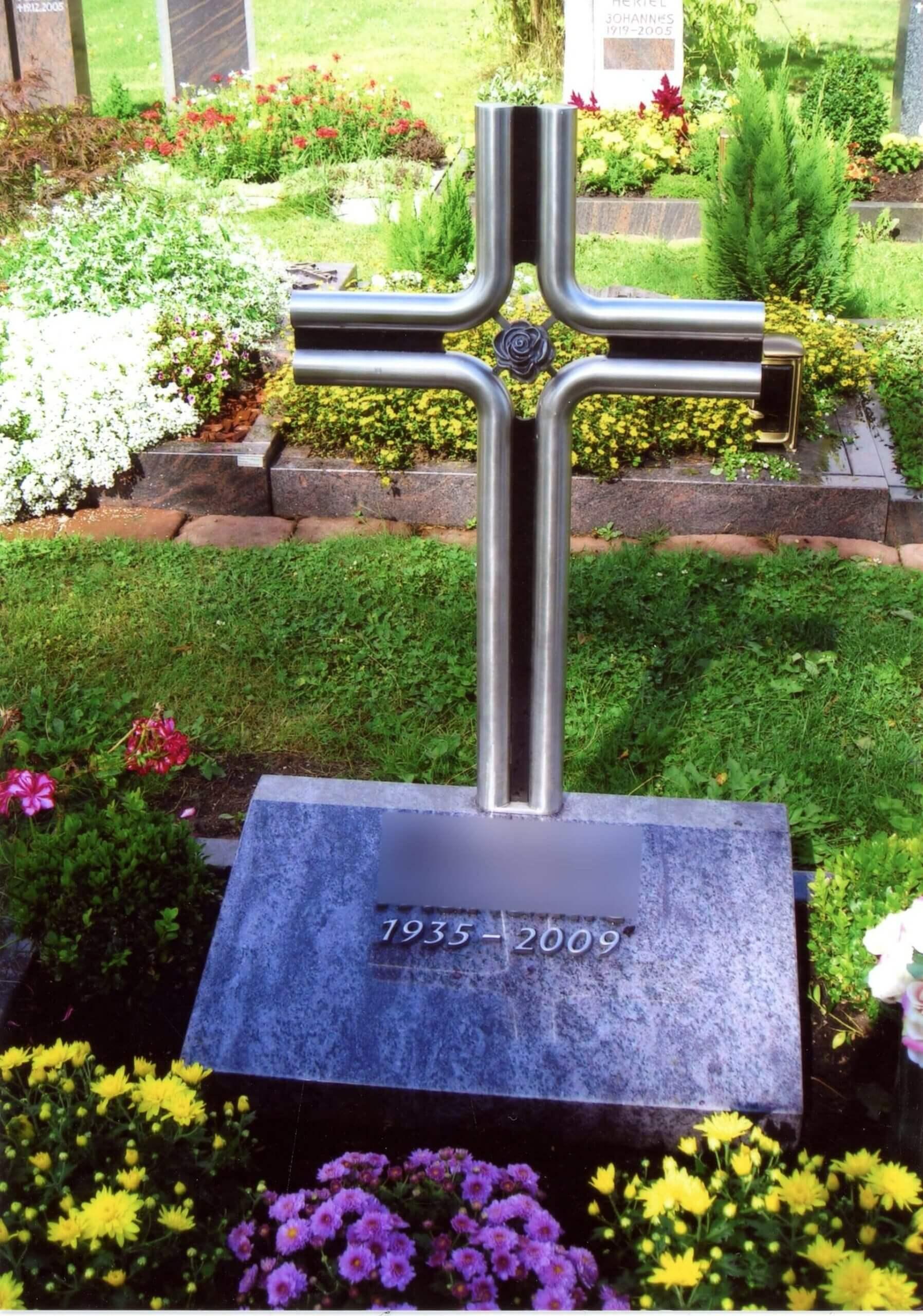 Kreuz aus Metallstangen auf Grabstein