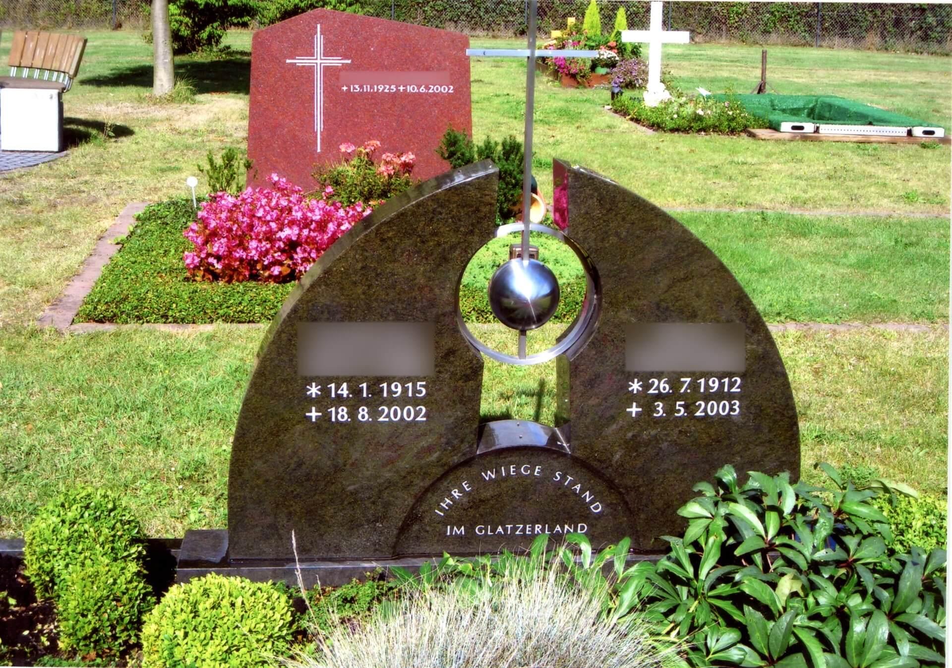 Kreuz mit Silberkugel auf braunem Grabstein