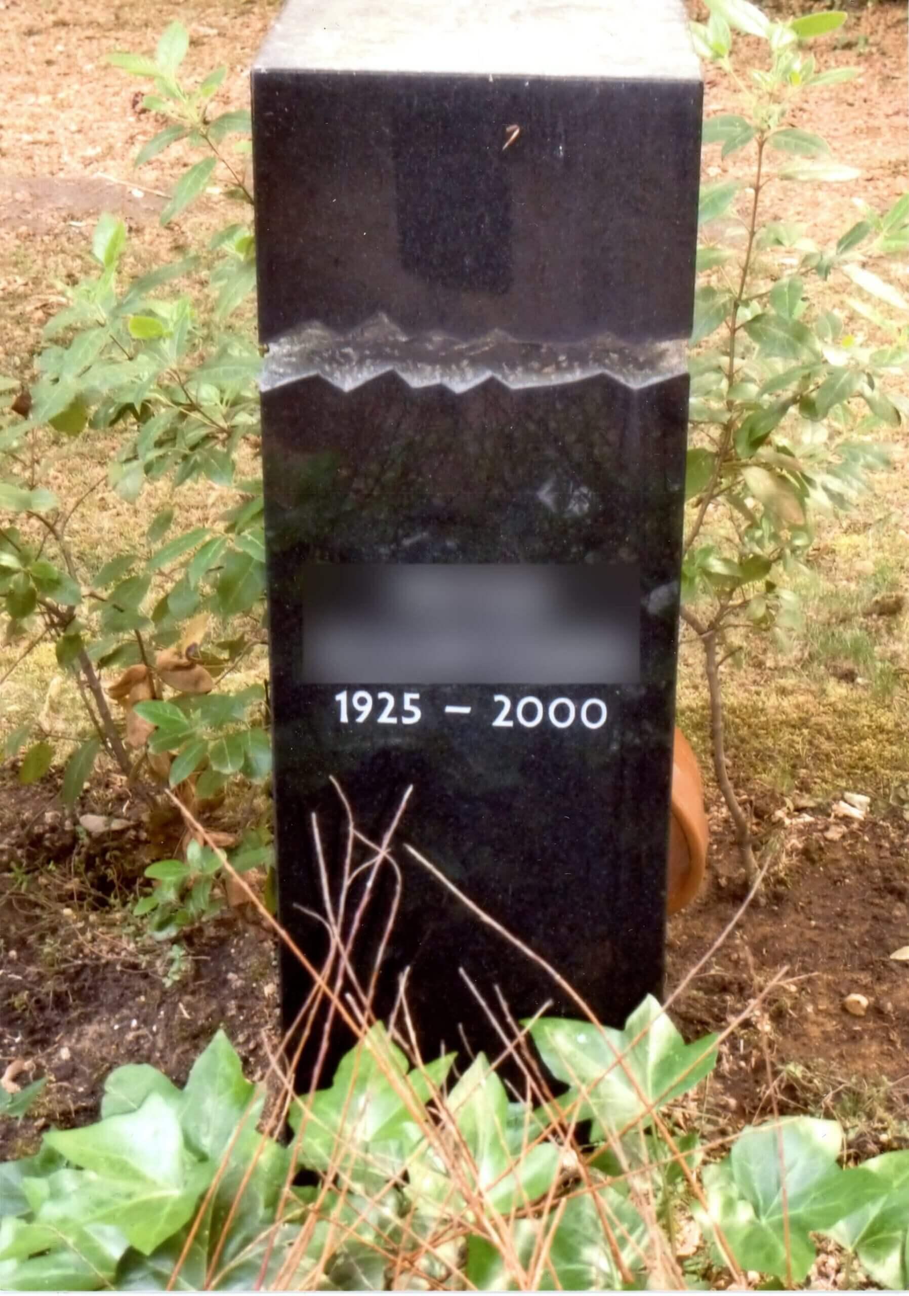 Schwarzer Grabstein in der Erde