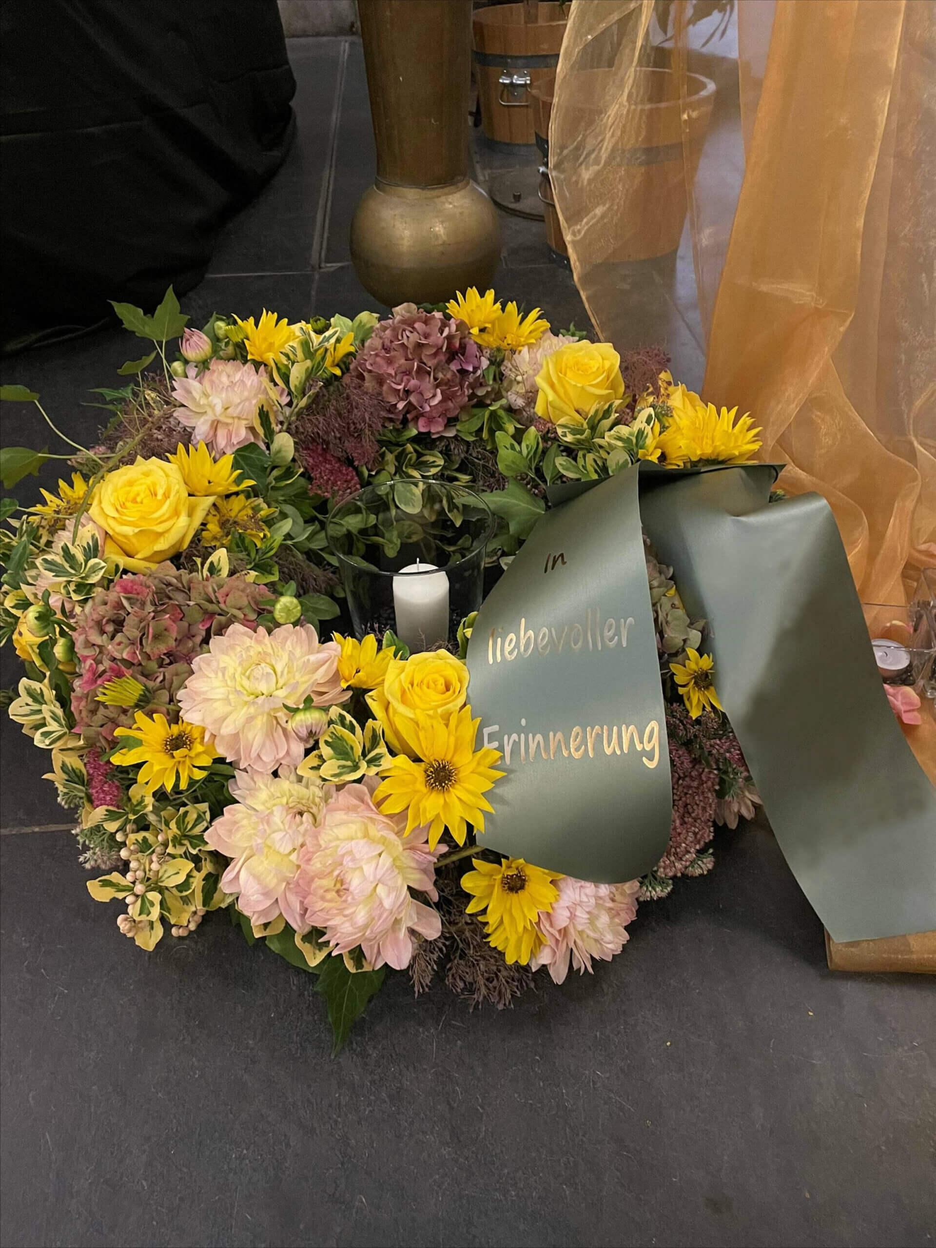 Sonnenblumen an Trauerkranz mit weißer Kerze