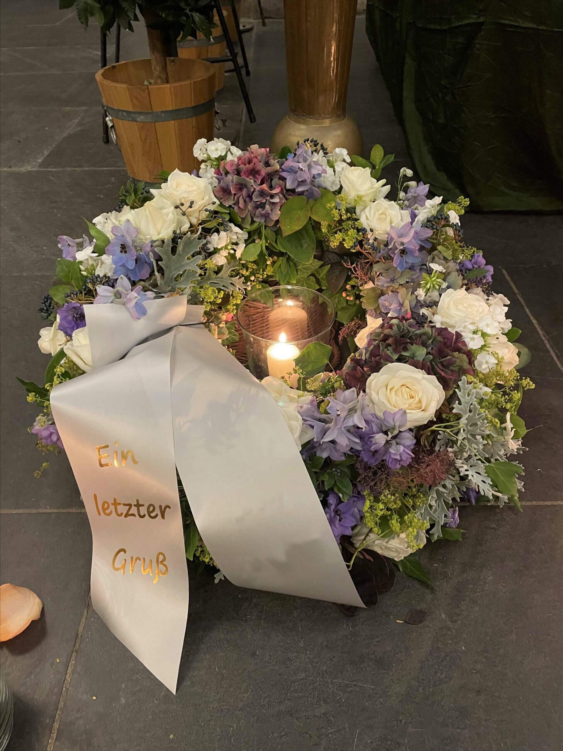 Weiße Schleife um Trauerkranz mit brennender Kerze